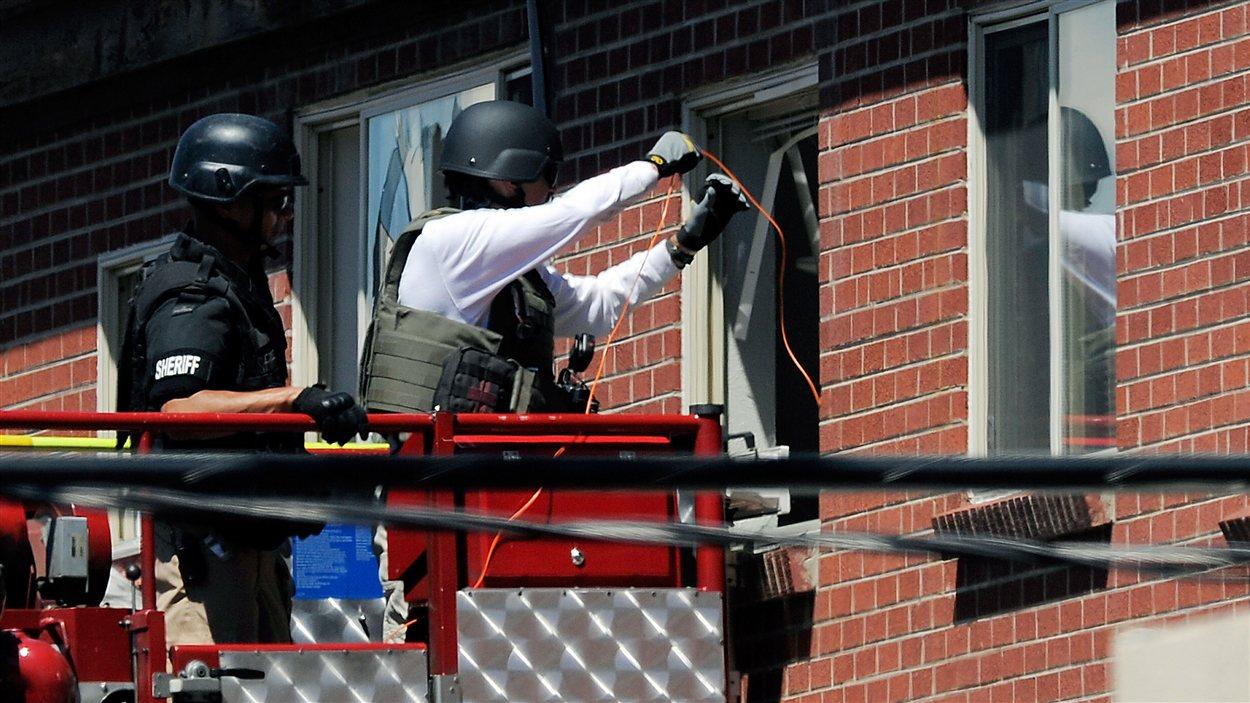 Les policiers tentent de neutraliser ce qui peut être dangereux dans l'appartement du suspect, samedi après-midi le 21 juillet 2012.