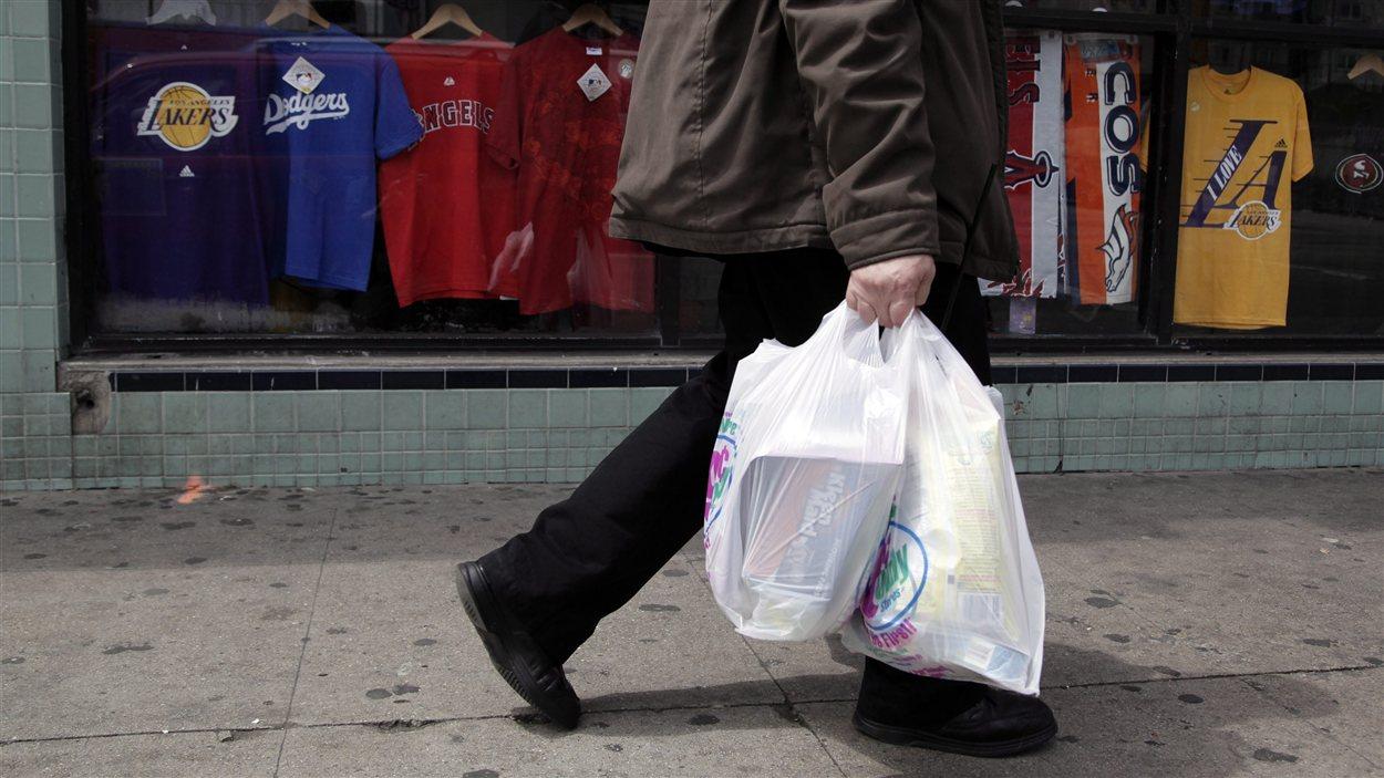 Sacs de plastique dans les mains d'un passant.