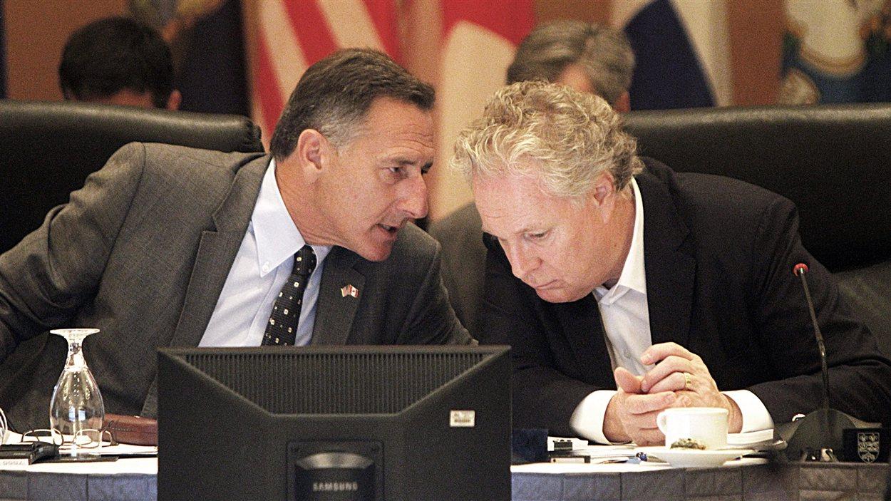 Le gouverneur du Vermont, Peter Shumlin, discute avec le premier ministre québécois, Jean Charest, lors de la rencontre à Burlington, le 30 juillet.