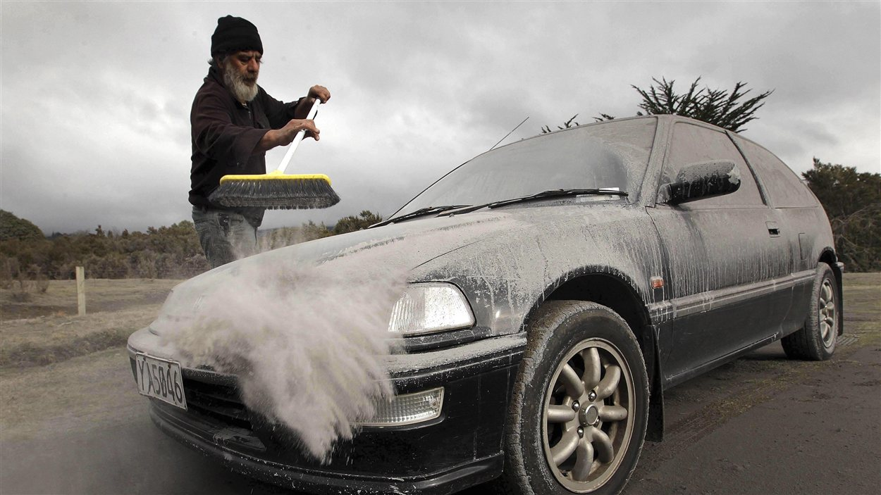 Un Néo-Zélandais balaie les cendres sur son véhicule après l'éruption d'un volcan situé sur le mont Tongariro, sur l'île du Nord, le 7 août 2012.