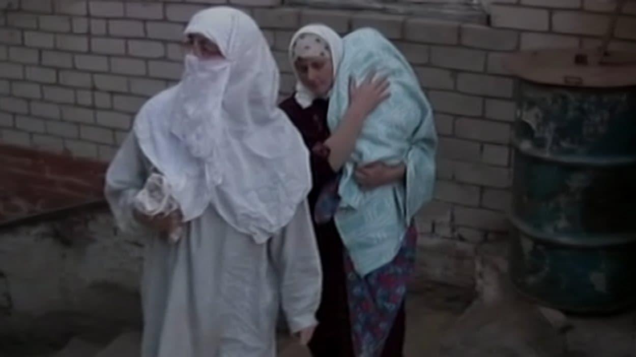 Des femmes et un enfant, membres de la secte, lors de leur sortie de l'abri souterrain.