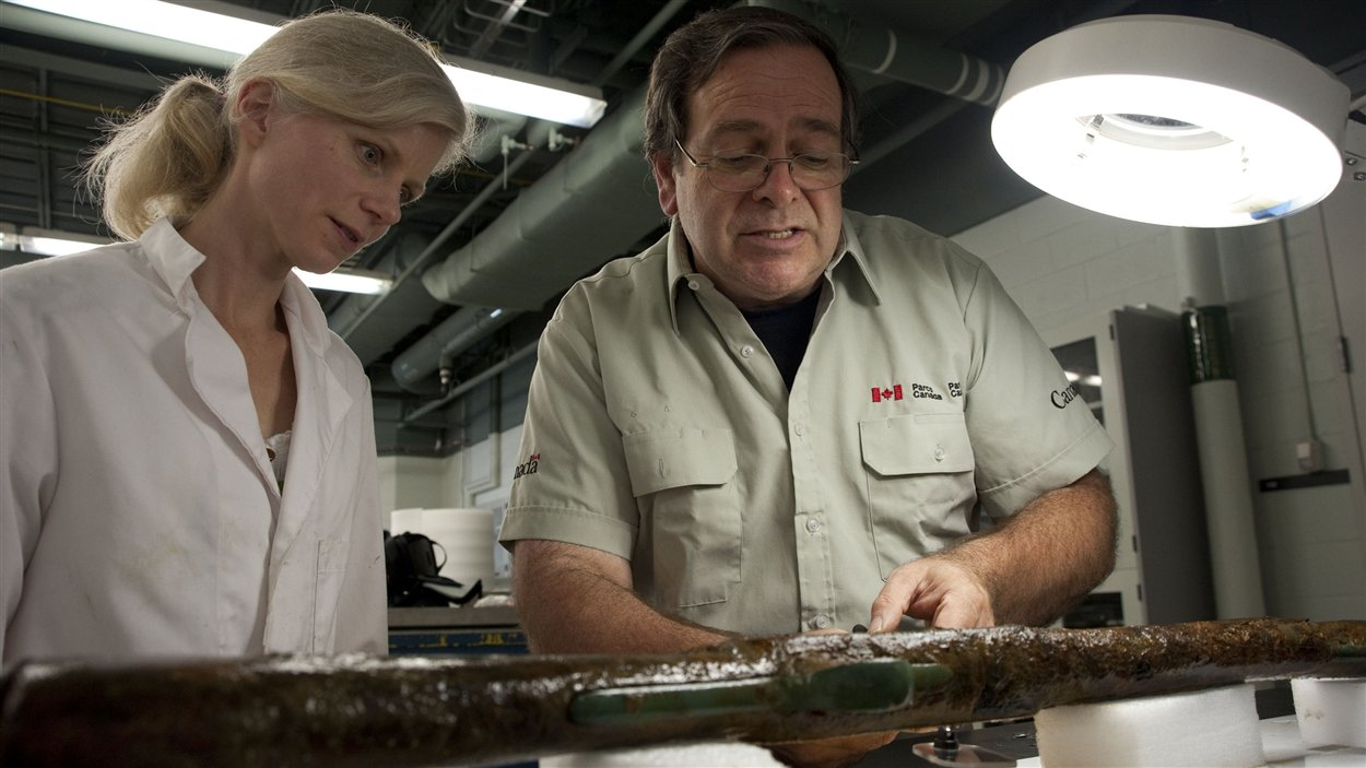 Des scientifiques examinent les vestiges d'une arme à feu.
