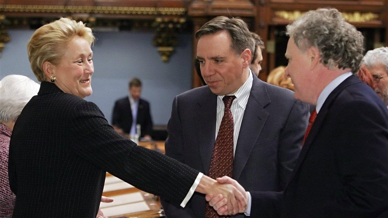 Le premier ministre Jean Charest serre la main de la députée Pauline Marois quelques minutes avant l'annonce de sa démission. Entre les deux, on peut voir François Legault, alors député péquiste. (2006)