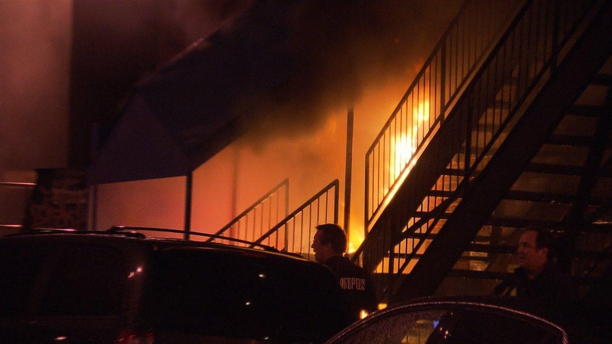 Des agents de sécurité du Métropolis arrivent sur les lieux de l'incendie allumé derrière l'immeuble.