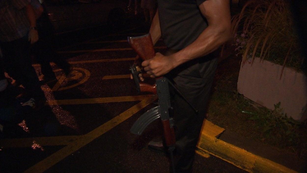 Un gardien de sécurité du Métropolis tient les armes lâchées par le suspect lors de son interception par les forces de l'ordre.