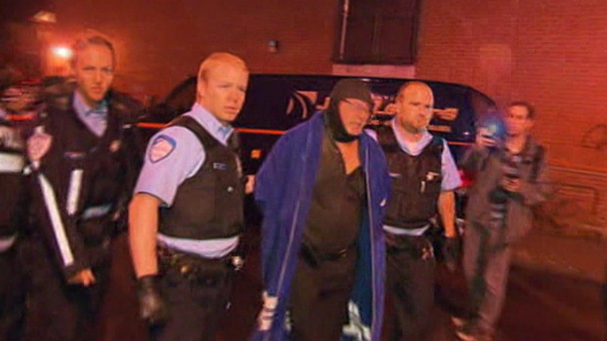 Le suspect est escorté par les agents du Service de police de la Ville de Montréal.