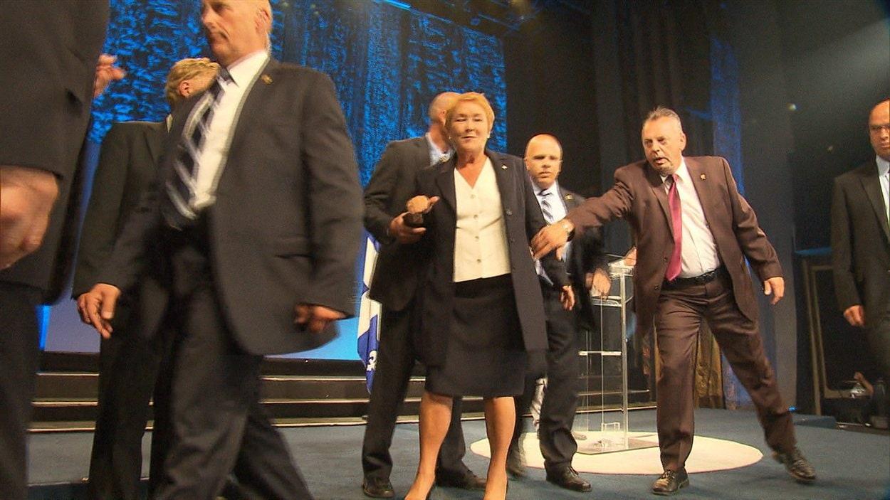 Pauline Marois insiste pour retourner sur scène et demander à ses militants de quitter les lieux dans le calme.