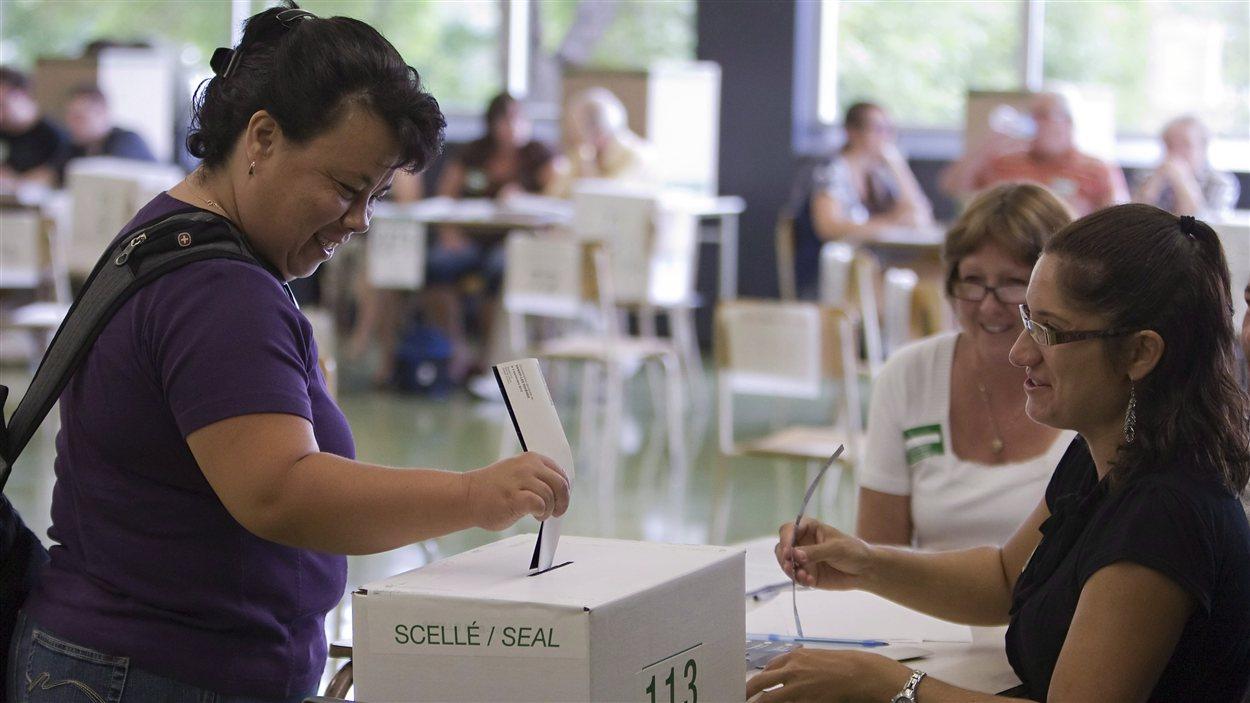 Une électrice dépose son bulletin de vote dans l'urne dans la circonscription de Vanier-Les Rivières.