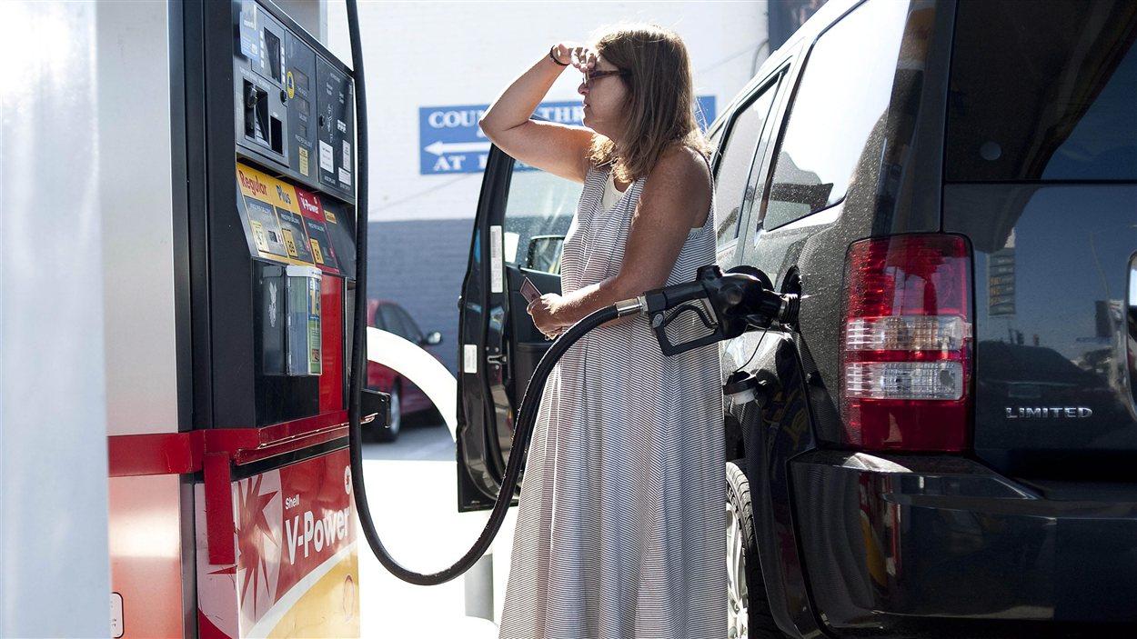 Une femme fait le plein d'essence.
