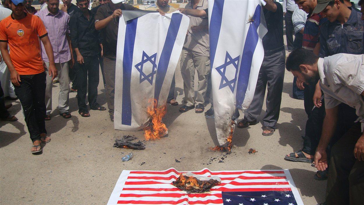 Des manifestants en Irak, dans la ville de Kut, brûlent des drapeaux américains et israéliens pour dénoncer le film controversé