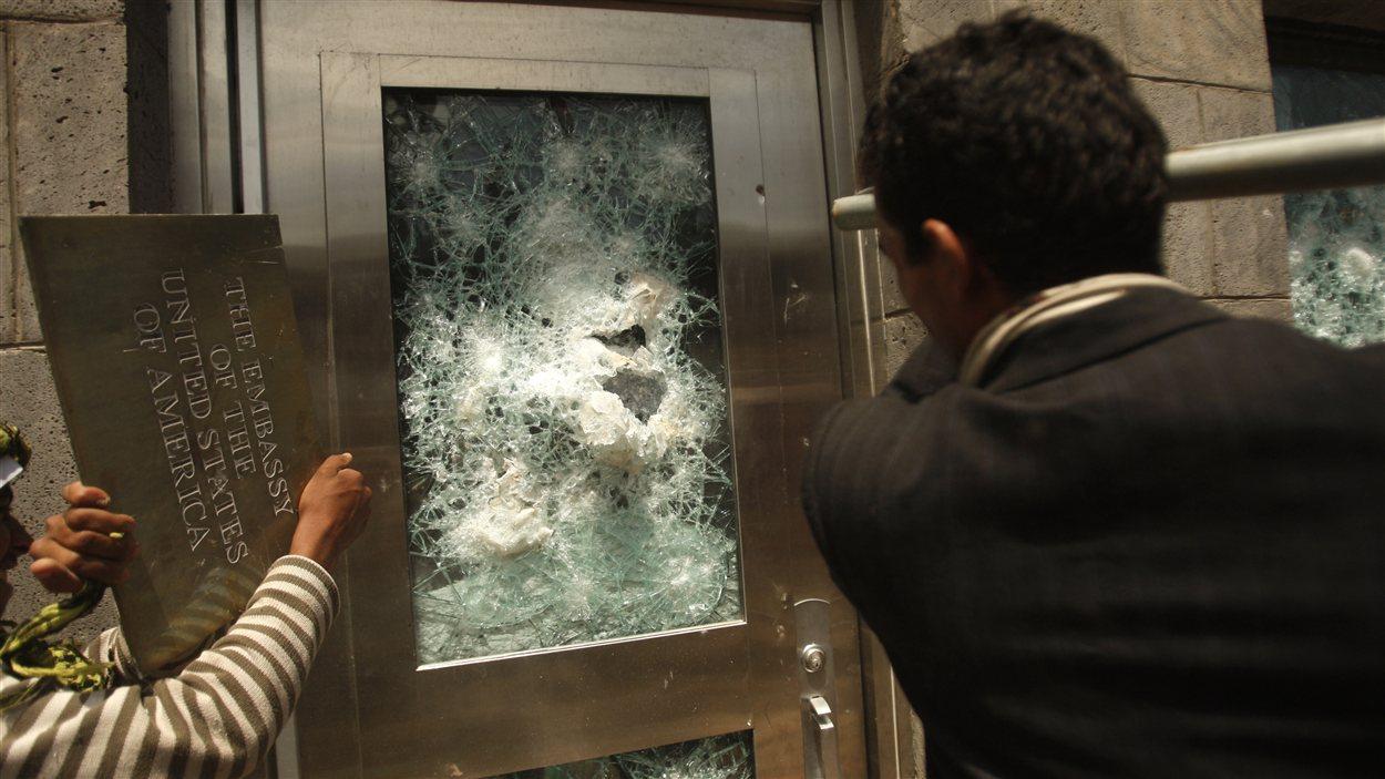 Au Yémen, un protestataire tente de fracasser la porte de l'ambassade américaine à Sanaa.