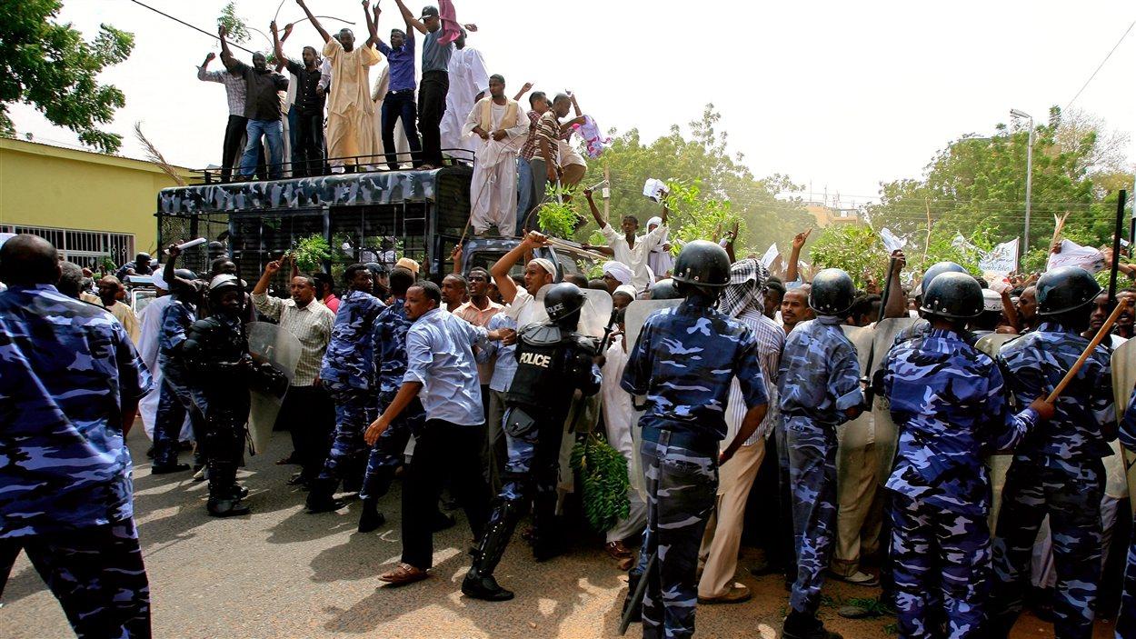 Vendredi, les forces de sécurité tentent de contenir la foule de manifestants près de la grande mosquée de  Khartoum, au Soudan.
