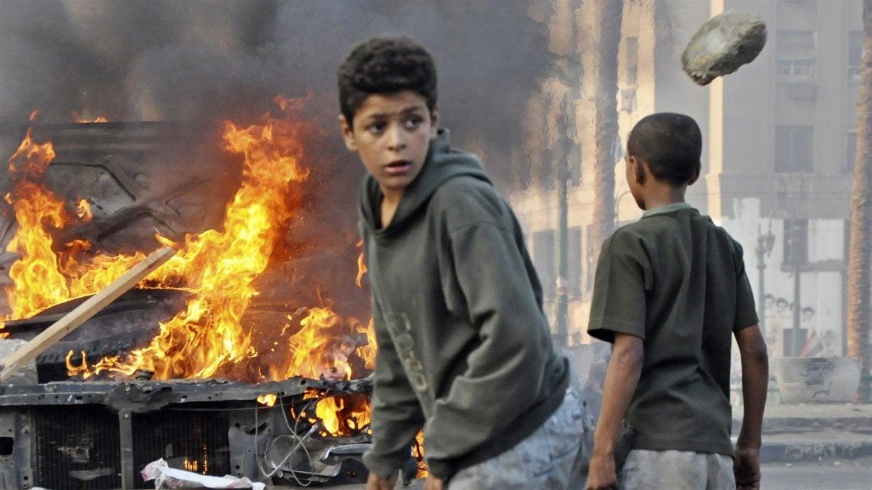 Des jeunes Égyptiens se rassemblent devant une voiture en feu au centre du Caire, tôt samedi.