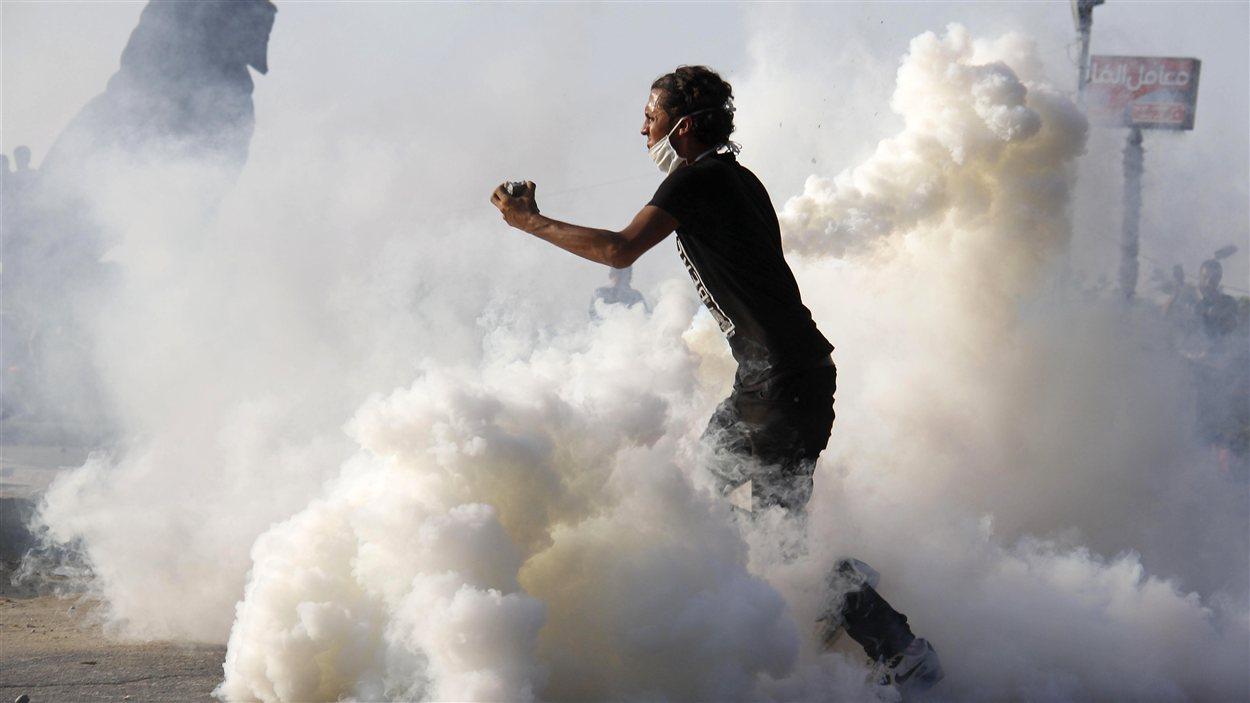 Au Caire vendredi, un manifestant lance une pierre contre les forces de sécurité, qui ripostent par des tirs de gaz lacrymogènes.