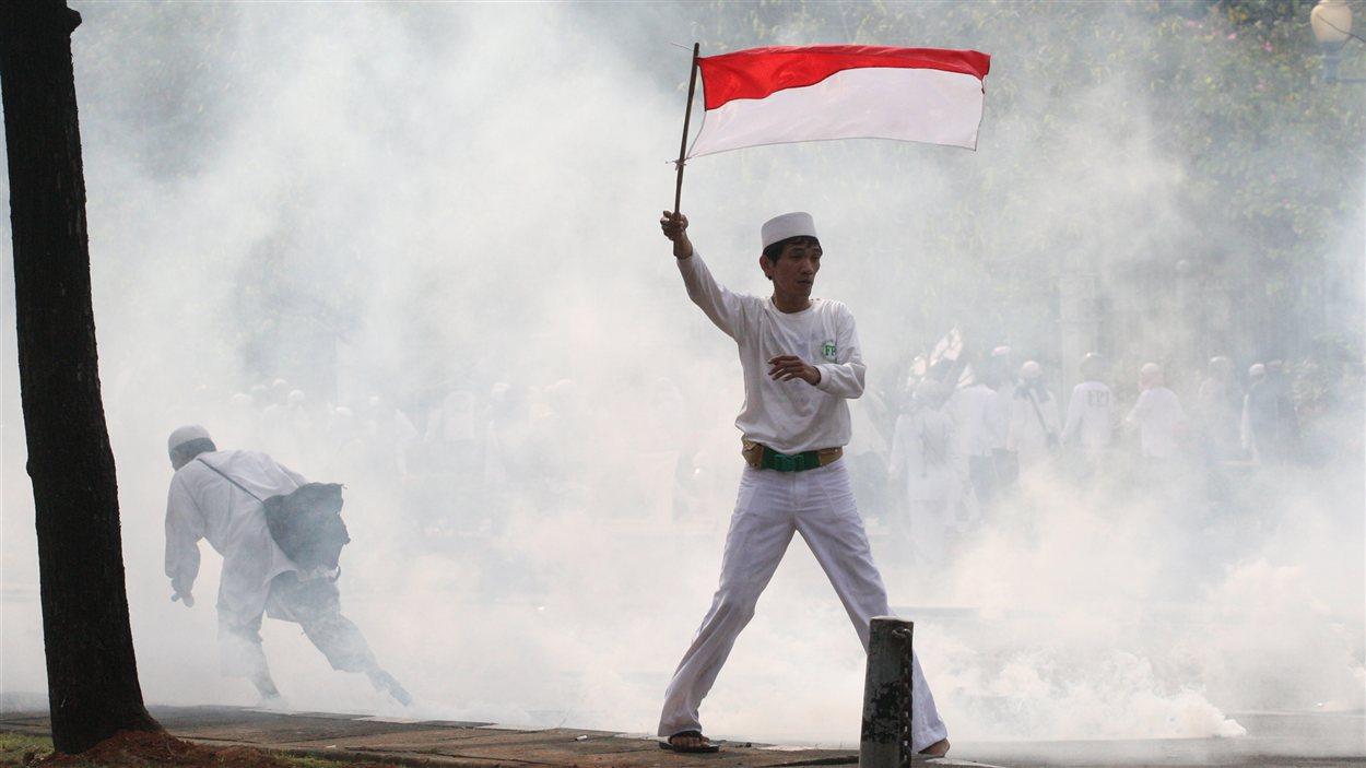 Un homme brandit un drapeau indonésien pendant une manifestation contre un film islamophobe, devant l'ambassade des États-Unis à Jakarta, lundi.