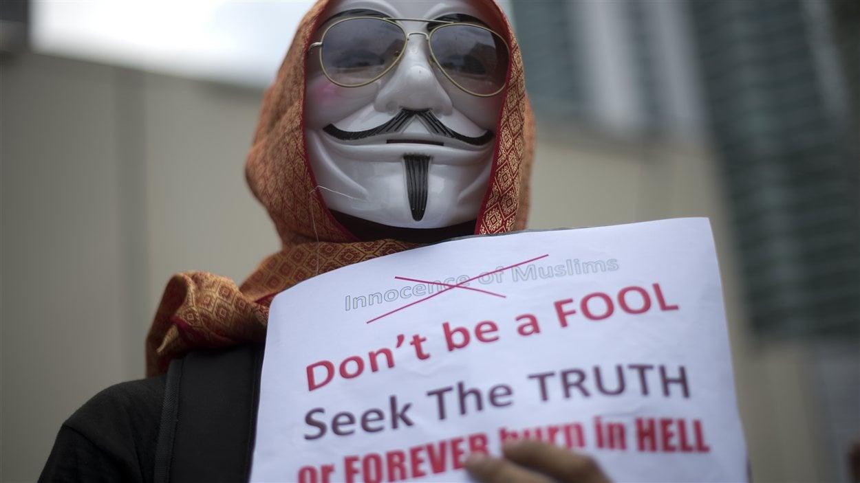 Un manifestant masqué devant l'ambassade américaine à Kuala Lumpur, en Malaisie.