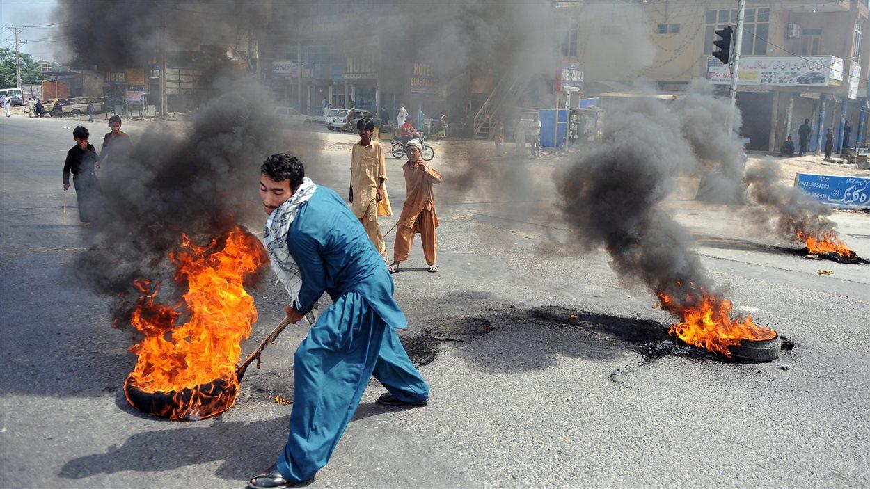 Au Pakistan, un manifestant tire des pneus en feu à Rawalpindi.