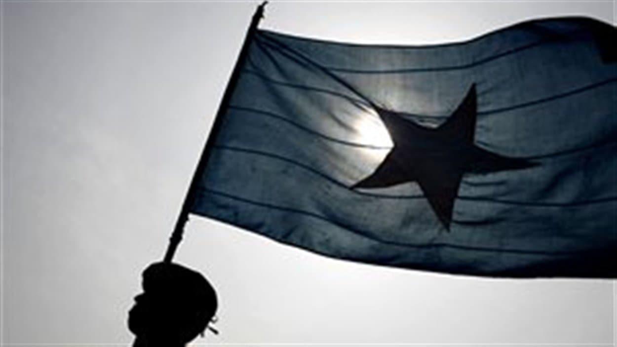 Un policier brandissant le drapeau de la Somalie en 2007.