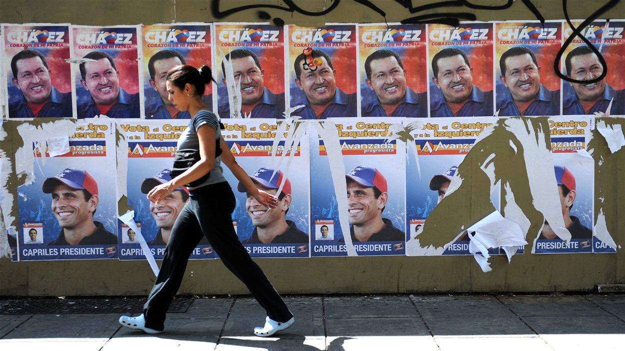 Une Vénézuélienne en train de marche devant des affiches du président sortant Hugo Chavez et du candidat de l'opposition Henrique Capriles, à Caracas.