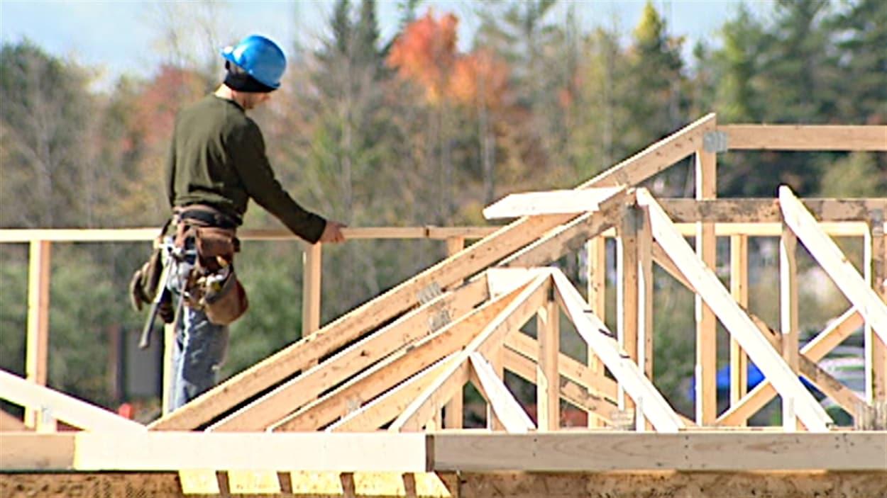 Un employé de la construction travaille sur le toit d'une résidence à Gatineau.
