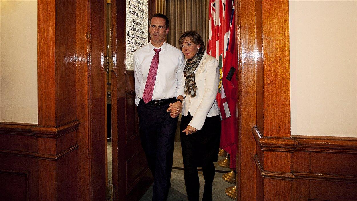 Le premier ministre Dalton McGuinty sort de la réunion d'urgence tenue avec son caucus en compagnie de son épouse.