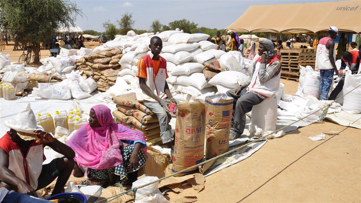 Des Maliens près d'un convoi humanitaire dans un camp de réfugiés, à 185 km de Ouagadougou.
