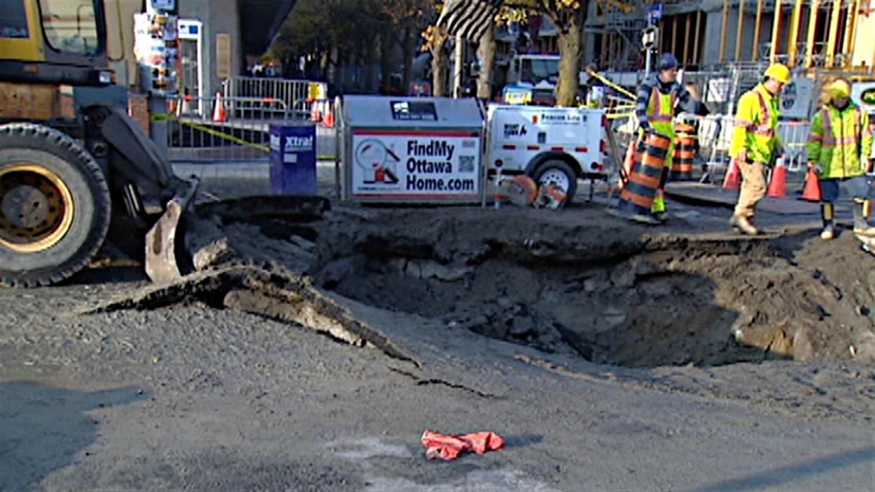 Les employés de la voierie travaillent à réparer l'important bris d'une conduite d'eau sur la rue Elgin, à Ottawa.