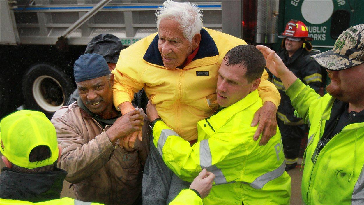 Un homme âgé est secouru par des pompiers volontaires à Atlantic City, au New Jersey, lors du passage de la tempête Sandy