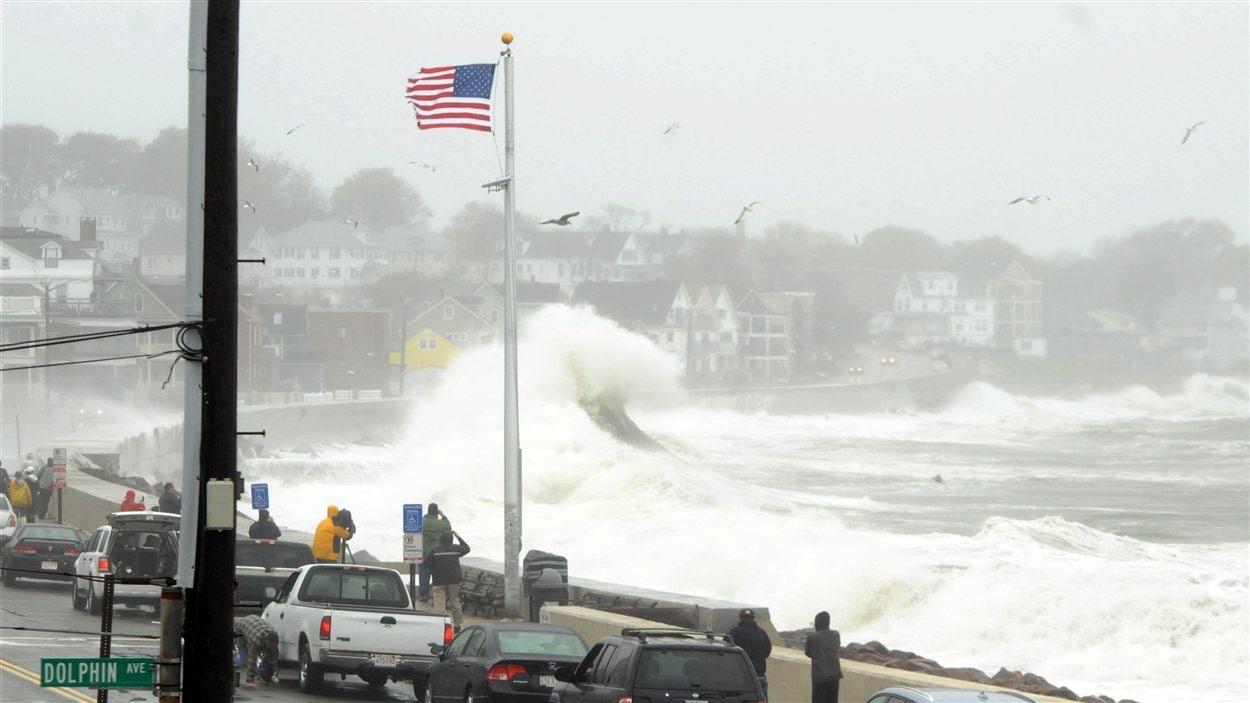 Les vagues frappent le long de la route à Winthrop, au Massachusetts, où des curieux regardent l'évolution de la tempête.