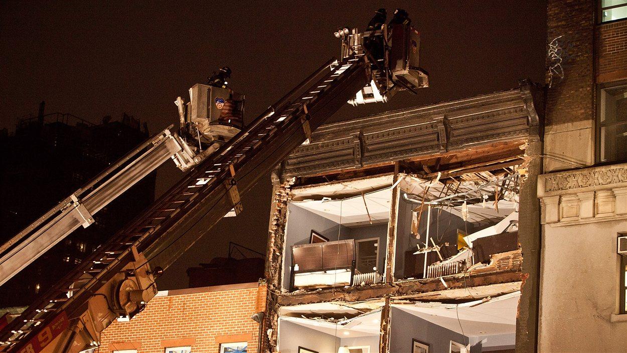 Des services de secours viennent en aide aux habitants d'un édifice dont la façade s'est effondrée lors du passage de la tempête Sandy, à New York