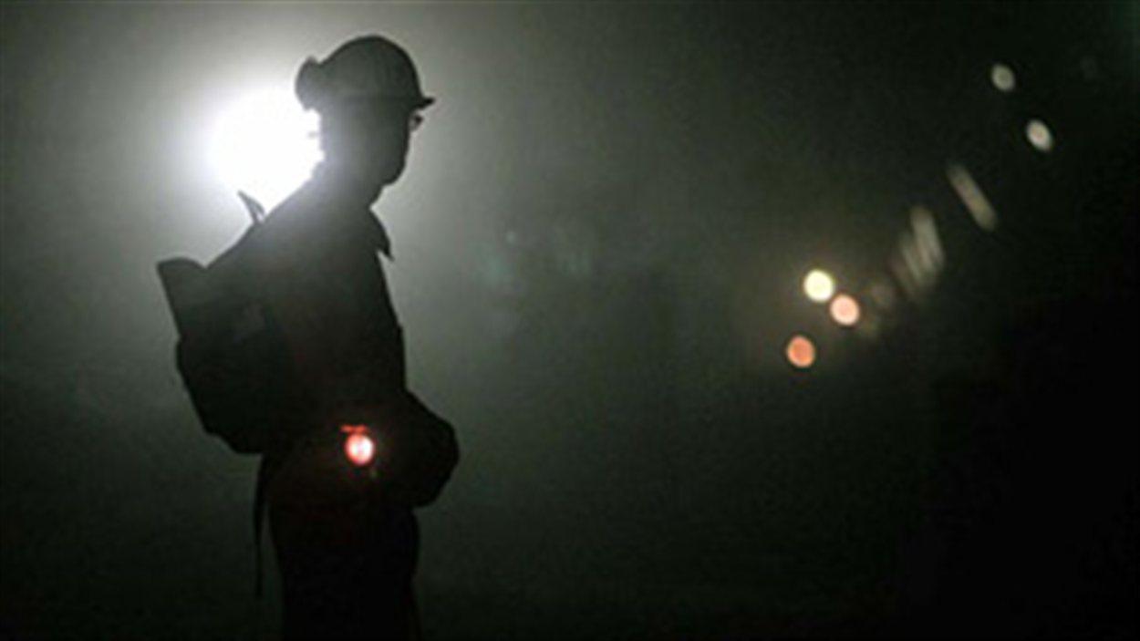 Un mineur debout dans un tunnel