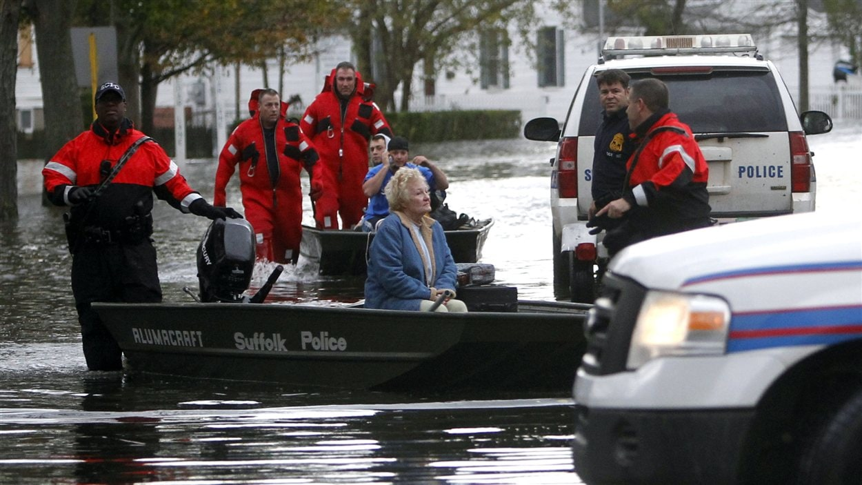 Des secouristes évacuent une femme âgée coincée dans sa maison par les eaux dans l'État de New York.