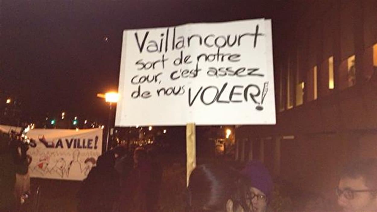 Pancarte tenue par une manifestante à l'extérieur de la séance du conseil municipal de Laval