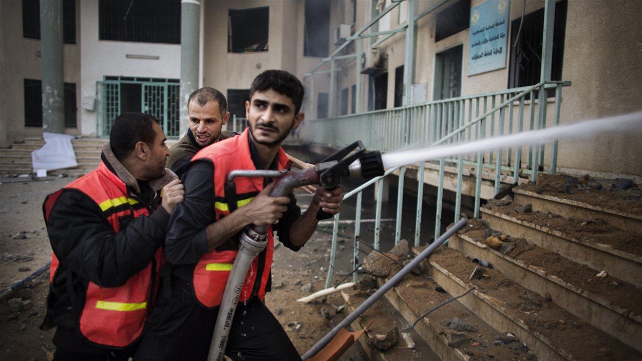 Des pompiers palestiniens tentent d'éteindre un incendie dans les locaux du ministère de l'Intérieur bombardé par les forces israéliennes.