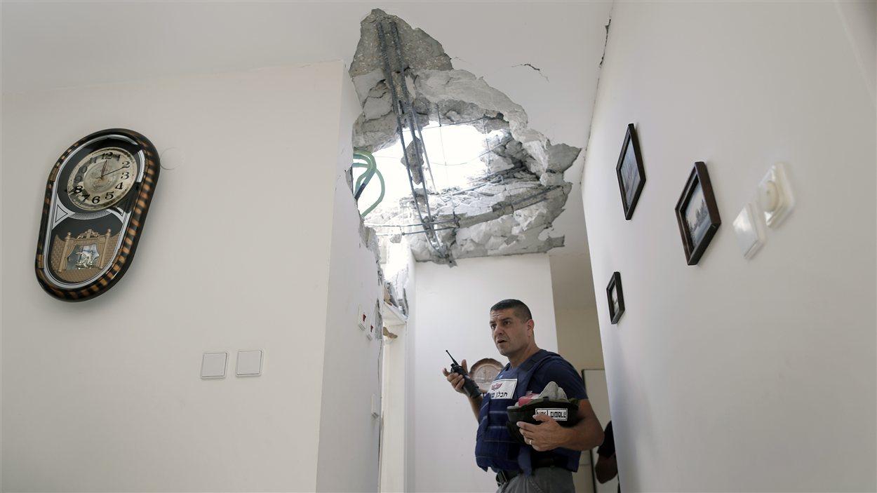 Un policier israélien dans une maison touchée par une roquette palestinienne dans la ville Ashkelon, dans le sud d'Israël, le 18 novembre.