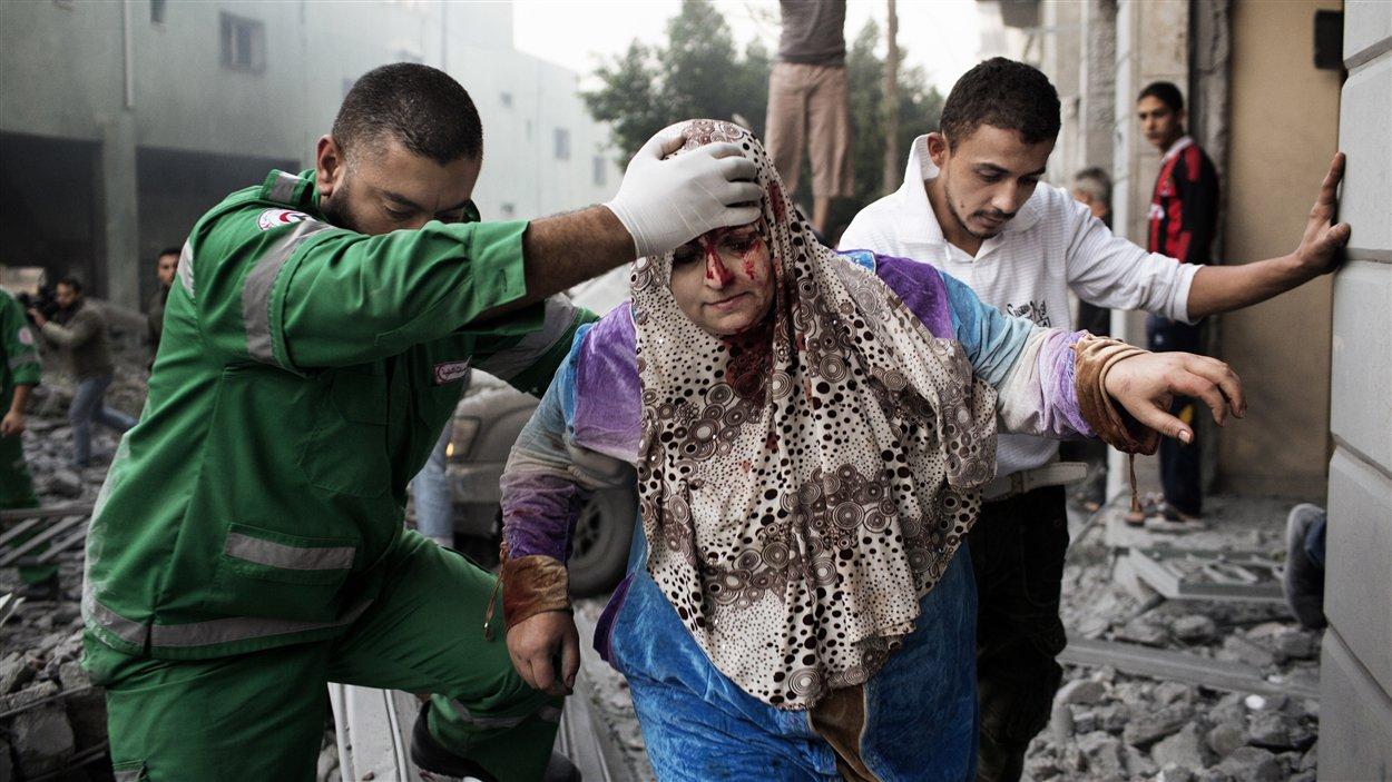 Une Palestinienne reçoit de l'aide d'un ambulancier pour sortir d'un immeuble visé par les raids israéliens dans le centre de la ville de Gaza le 19 novembre.