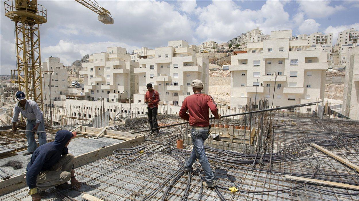 Des travailleurs érigent un complexe d'habitation à Jérusalem-Est.