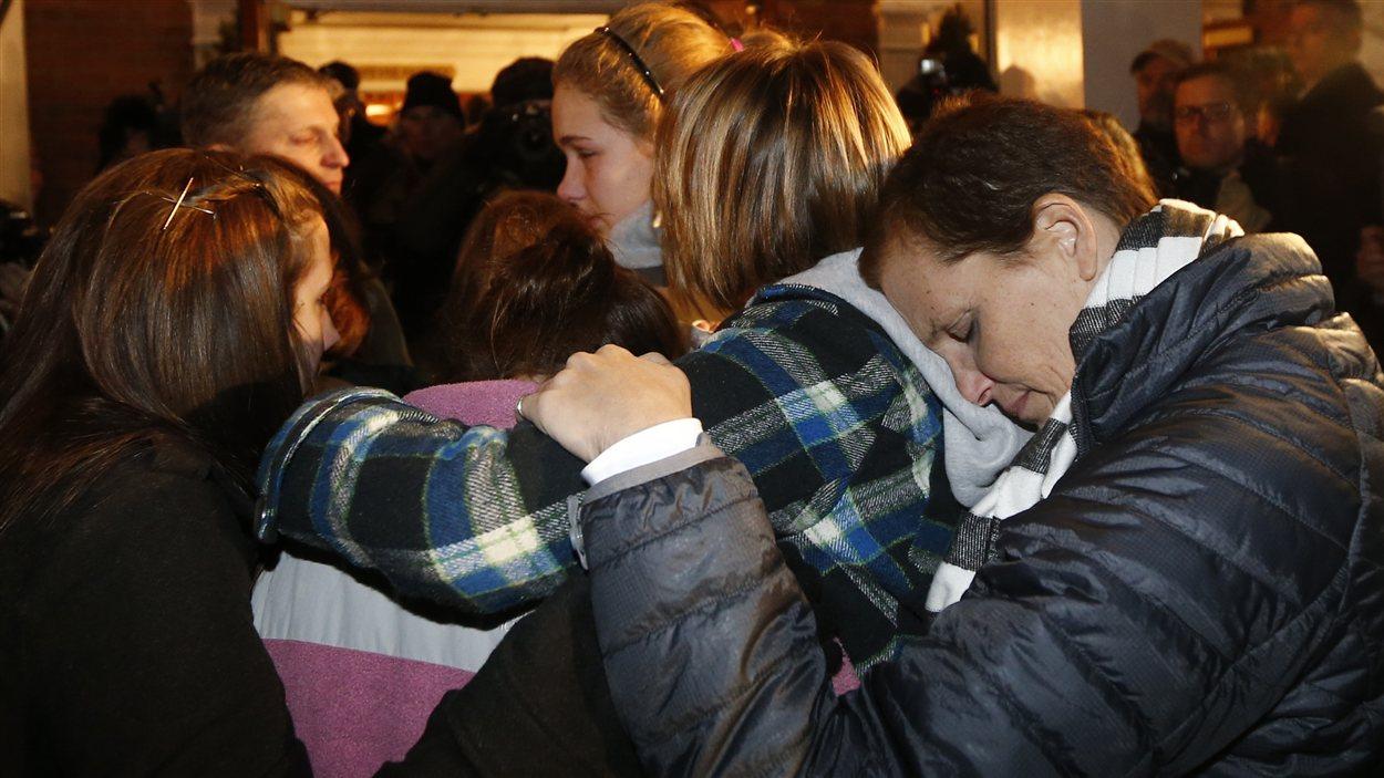 Des jeunes filles se réconfortent à l'église Sainte-Rose-de-Lima à Newtown, au Connecticut, lors d'une messe célébrée en hommage aux victimes de la tuerie de l'école Sandy Hook.