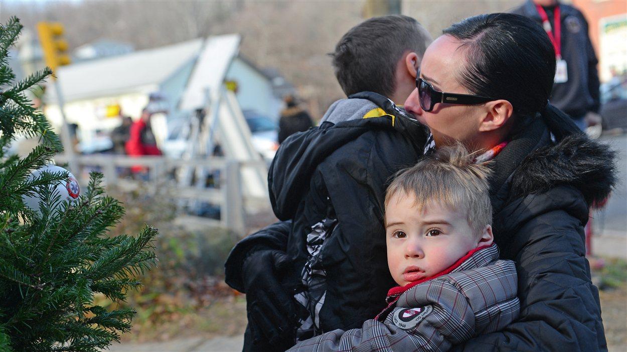 Une mère embrasse ses enfants après un hommage aux victimes de la tuerie.