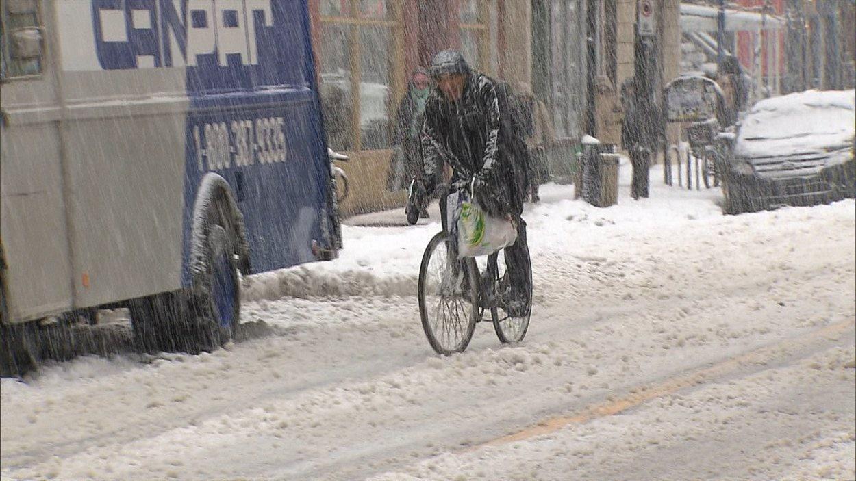 Un cycliste roule dans la neige dans une rue de Montréal