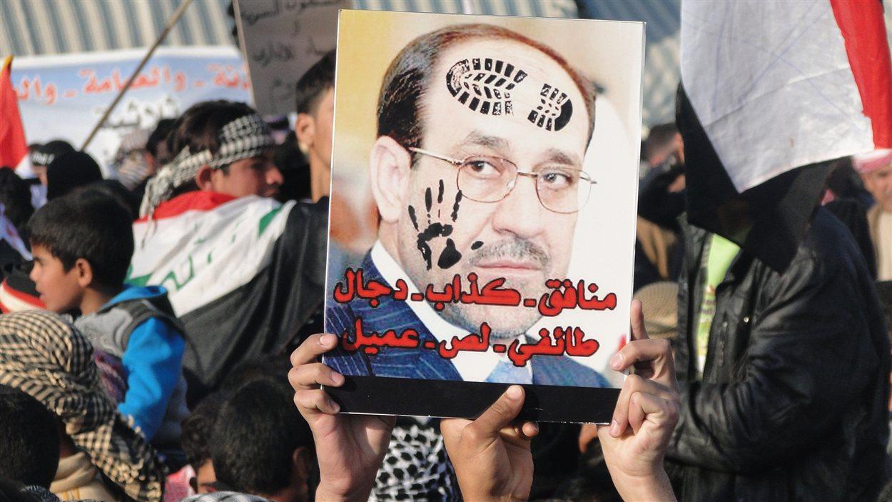 Des manifestants à Ramadi brandissant un portrait d'Al-Maliki où on peut lire « Hypocrite, menteur, sectaire, voleur, traitre »