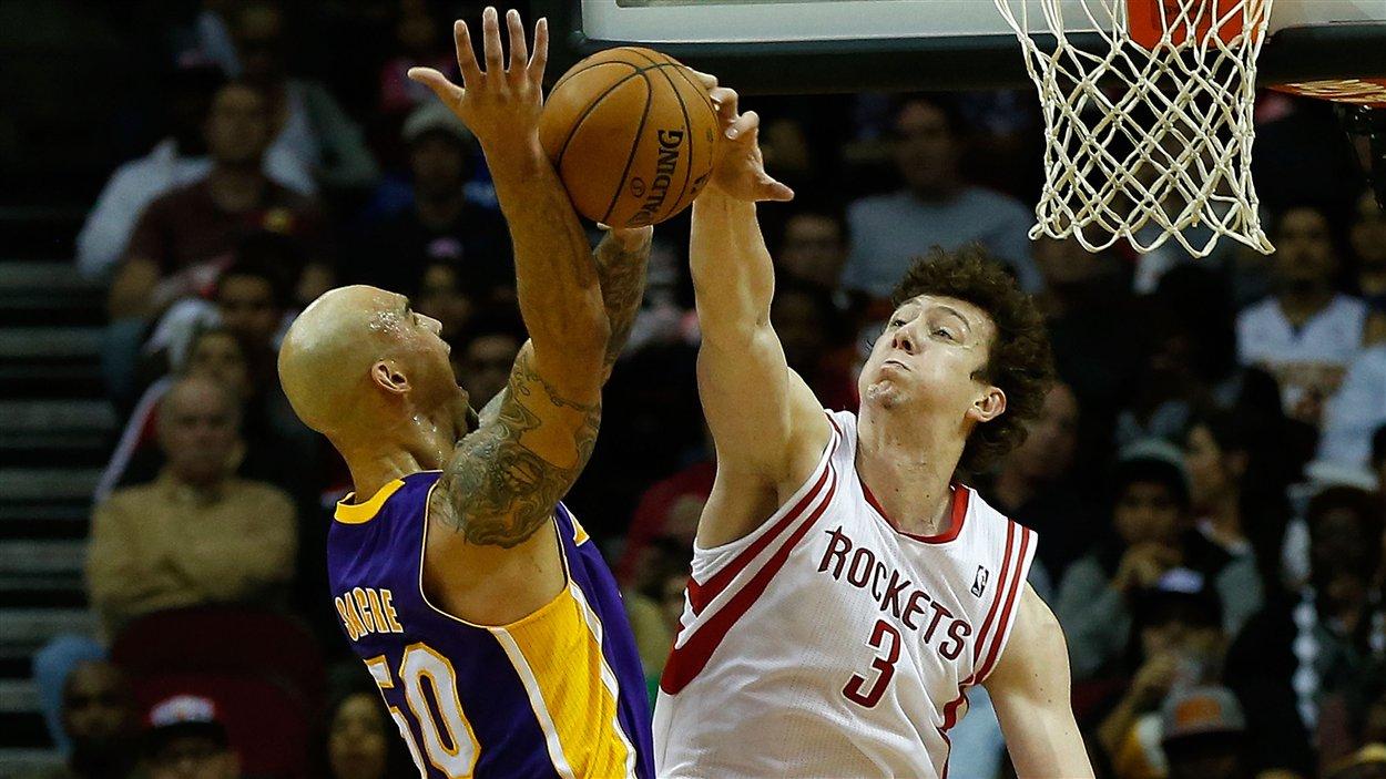 Robert Sacre (no 50) des Lakers voit son tir être bloqué par Omer Asik (no 3) des Rockets.
