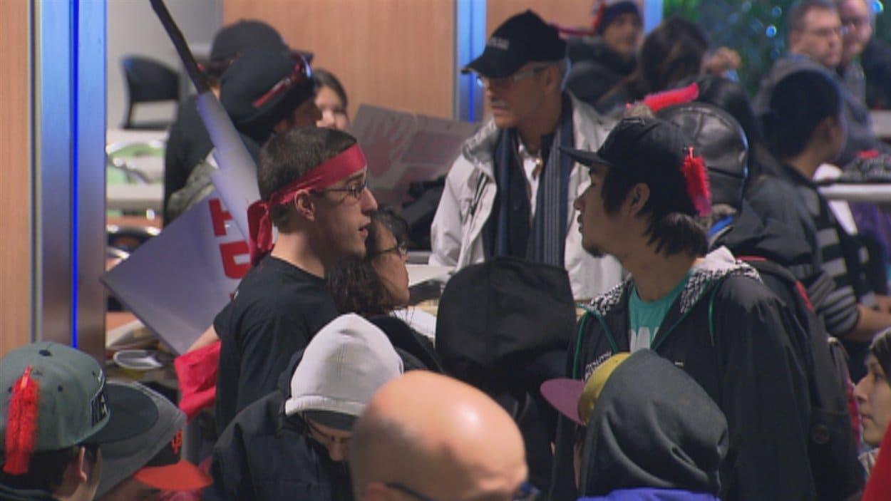 Des participants à la manifestation discutent à l'UQAC.