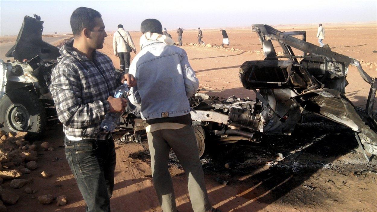 Des hommes examinent les restes d'un véhicule détruit près du site d'In Amenas, en Algérie.