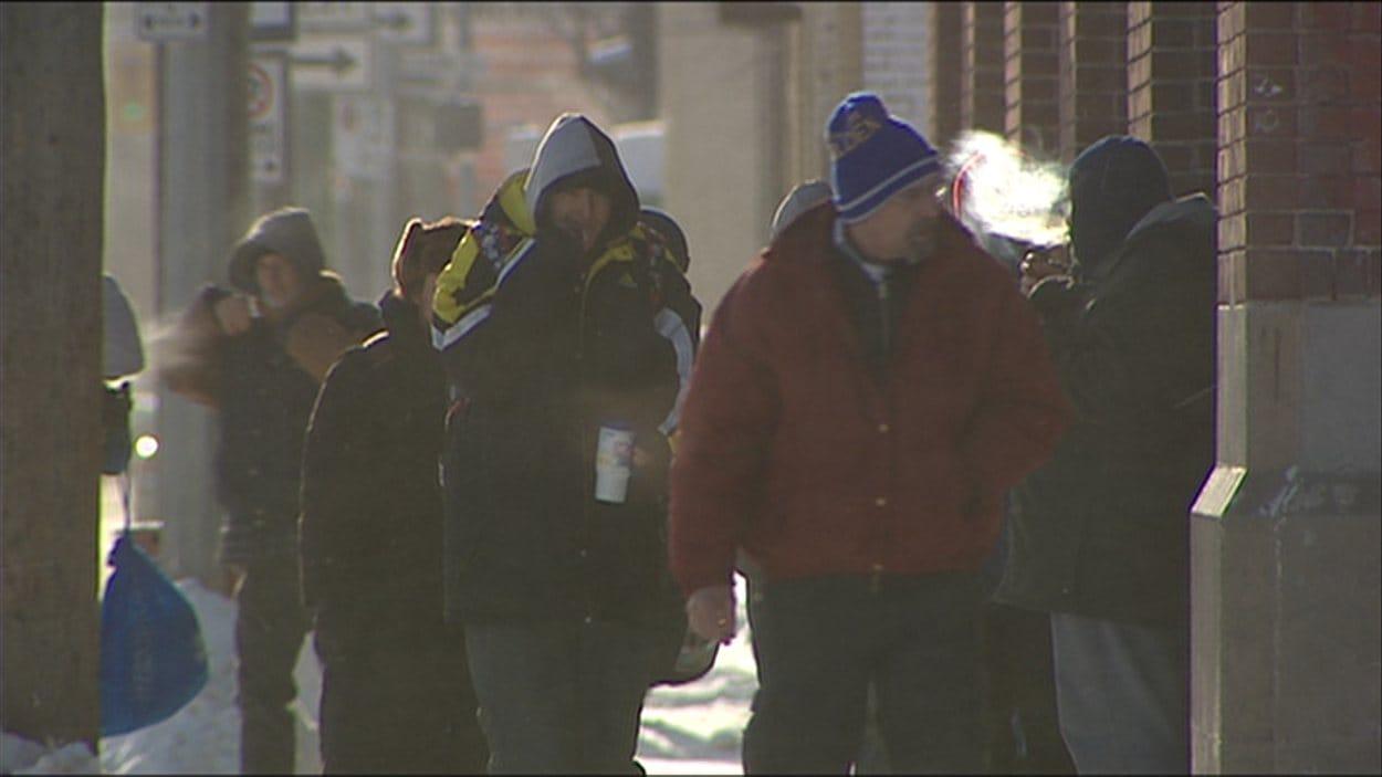 Des sans-abris tentent de se réchauffer aux abords d'un refuge.