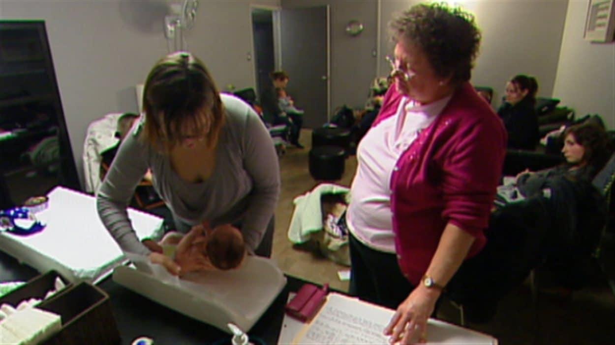 Une sage-femme guide une femme qui a récemment accouché dans sa maison de naissance