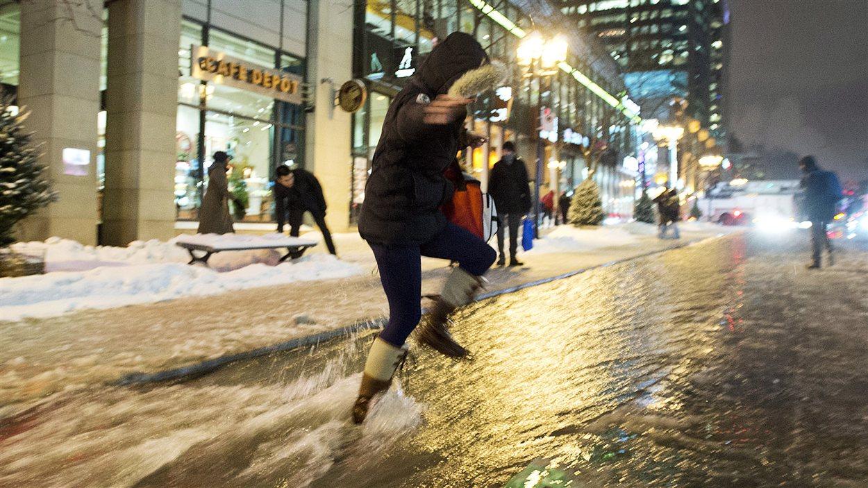 Une femme traverse la rue inondée à Montréal.