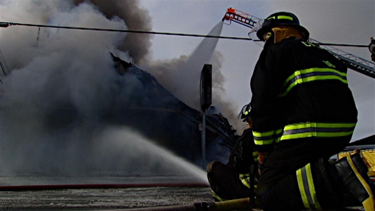 Un pompier lutte contre le brasier qui a détruit dimanche la fromagerie St-Albert.