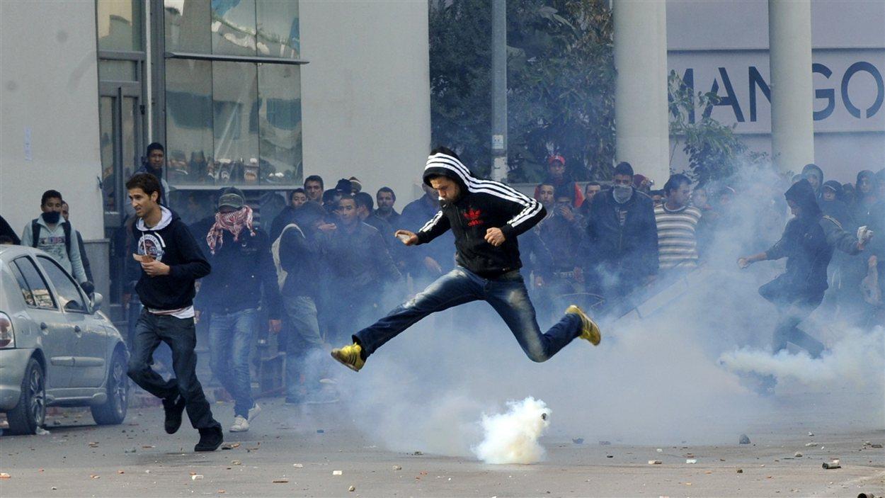 Un manifestant saute par dessus une bonbonne de gaz lacrymogènes lors d'une manifestation devant les bureaux du ministère de l'Intérieur à Tunis.