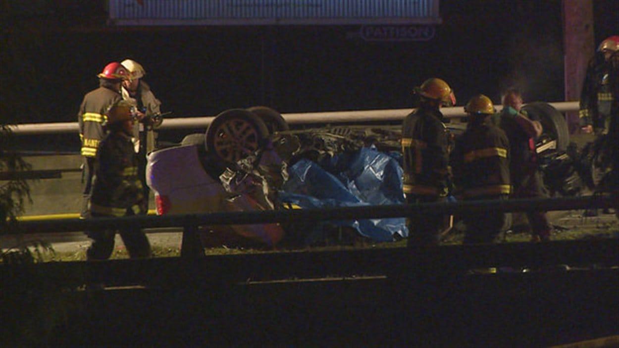 Des pompiers et des policiers sont sur le viaduc Georgia à Vancouver, tôt le matin du 8 février 2013, où une voiture a fait un accident mortel.